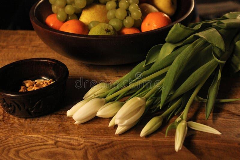 Ainda vida - fruto em uma bacia de madeira e em umas tulipas brancas em uma tabela de madeira fotografia de stock royalty free