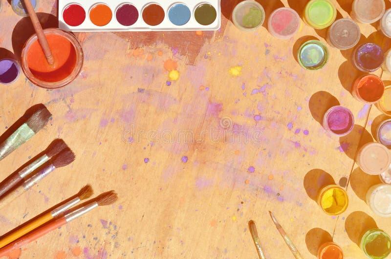 Ainda vida, mostrando um interesse na pintura e na arte da aquarela Muitas escovas, frascos com aquarela pintam e usaram a mentir imagens de stock royalty free