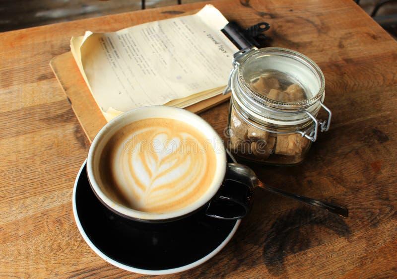 Ainda vida - objetos - xícara de café, menu e açúcar mascavado em um frasco de vidro fotografia de stock royalty free