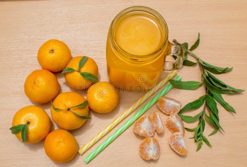 Ainda vida 1 Uma caneca transparente com um punho com suco recentemente espremido da tangerina E tangerinas frescas imagem de stock