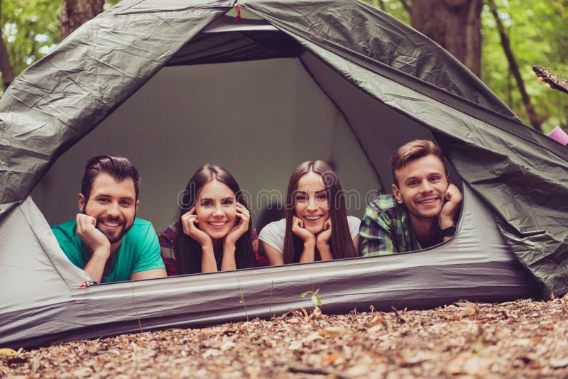 Ainsi amusement ensemble ! Deux beaux couples se couchant dans la tente dans a images stock