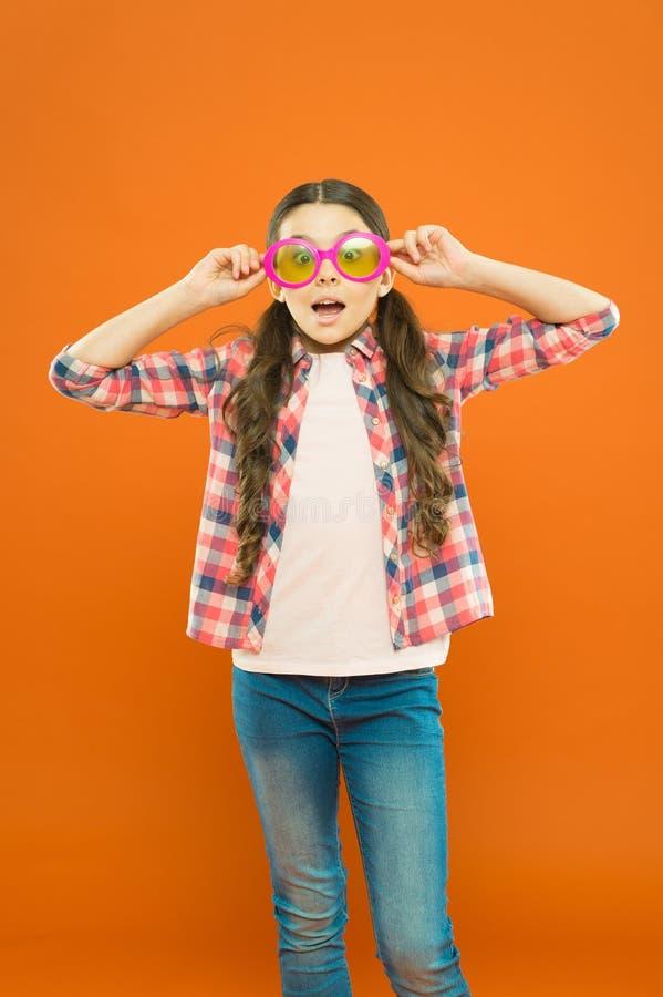 Aint det som ?r roligt Liten flicka som ser till och med roliga exponeringsglas med f?rgfiltret p? orange bakgrund Roligt b?ra f? arkivfoto