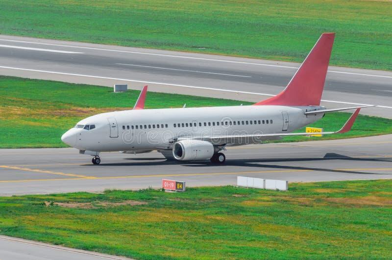Aiplane på landningsbanan, når att ha landat som åker taxi till terminalen på flygplatsen royaltyfri fotografi
