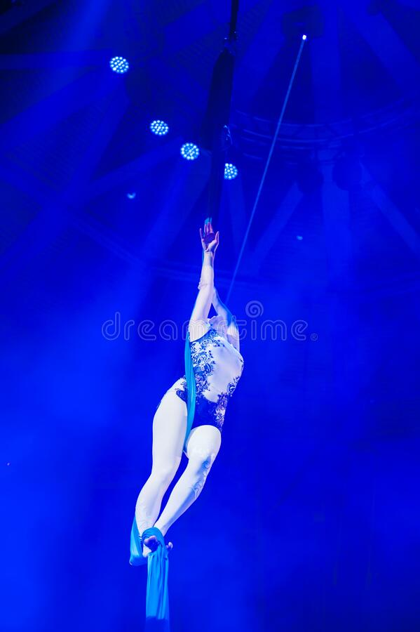 Air acrobat in the circus. A young girl performs the acrobatic elements in the air ring royalty free stock photo
