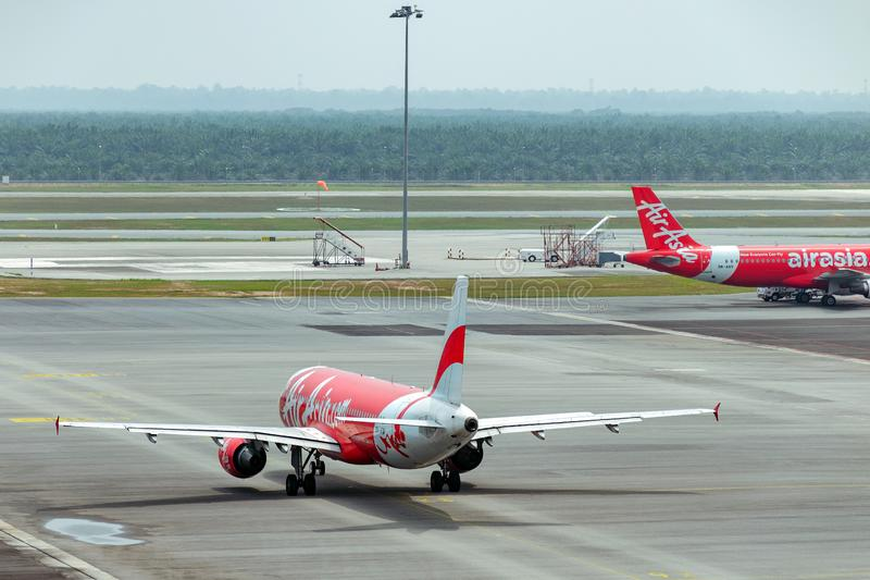 Air- Asiaflugzeug, das am Asphalt in Kuala Lumpur International Airport mit einem Taxi fährt lizenzfreie stockbilder