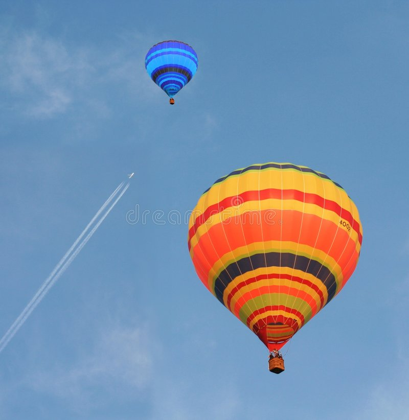 Air Balloons. On the blue sky with crossing aircraft royalty free stock photo