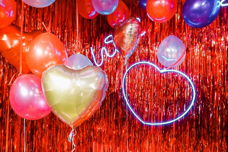 Air Balloons. Bunch of colorful purple, pink, blue heart shaped foil balloons with Heart Neon Light on red background. royalty free stock photos