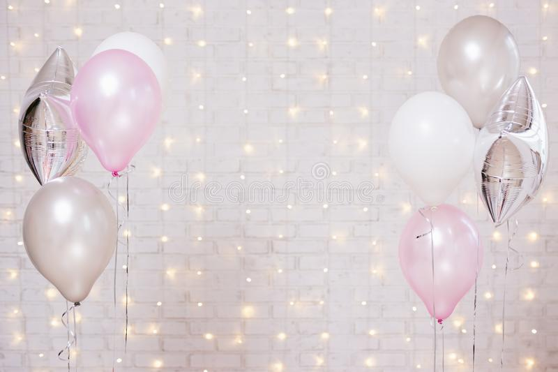 Air balloons over white brick wall background with lights royalty free stock photos