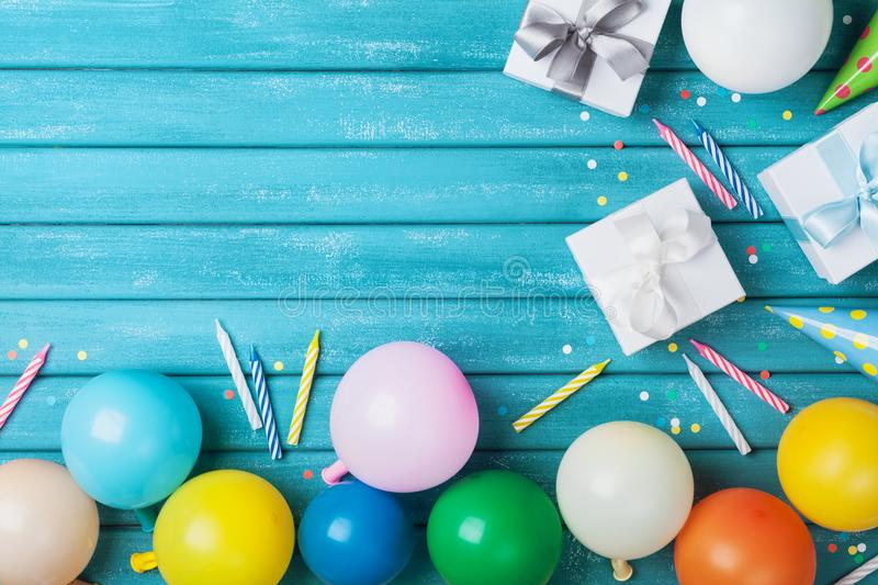 Air balloons, present or gift box, confetti and candle on vintage turquoise table top view. Birthday or party card. Copy space for text royalty free stock images