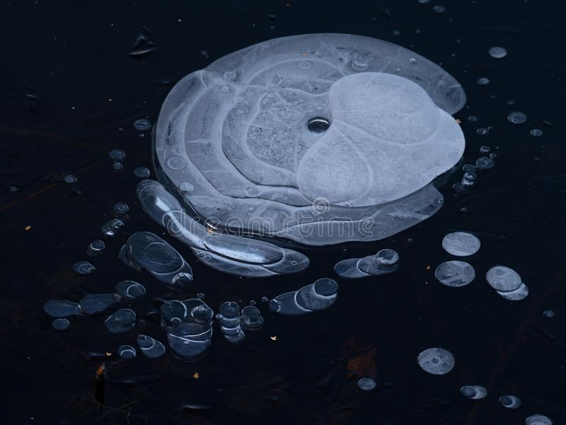 Air bubbles frozen uder ice. Natural art. Amazing shapes from air bubbles under ice and water wilderness throw stone season scenic reflection nature line stock photos