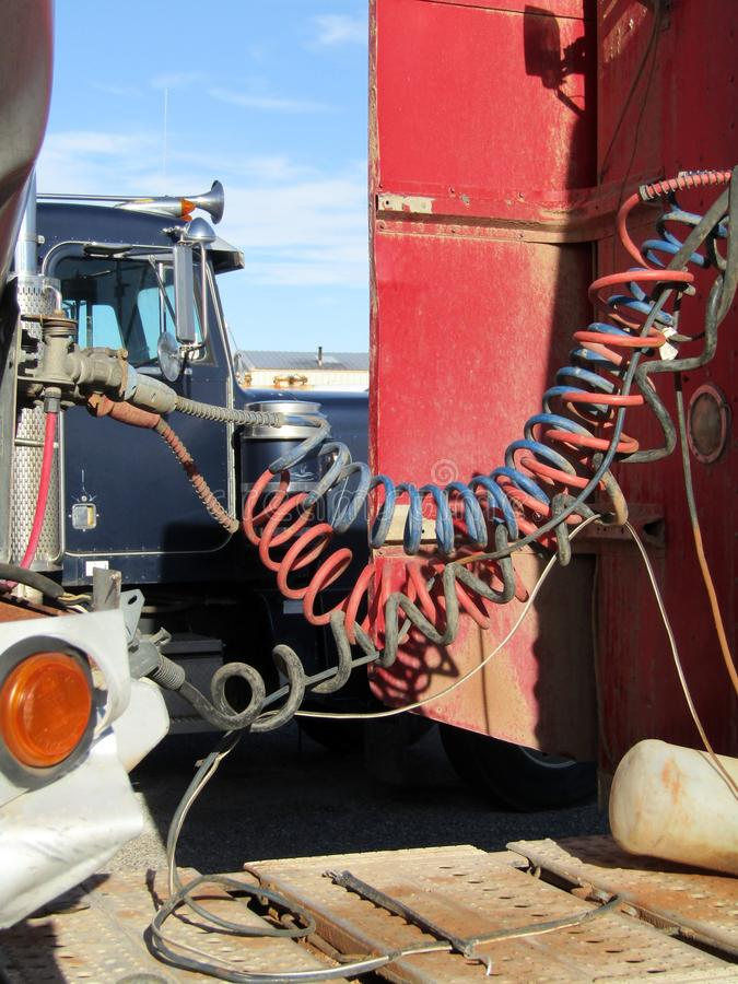 Air cables connecting semi truck and trailer. Black, red and blue air cables connecting truck and trailer royalty free stock image