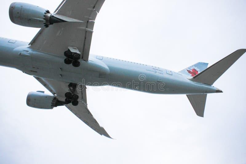 Air- Canadaflugzeug hochfliegend durch den Himmel lizenzfreie stockbilder
