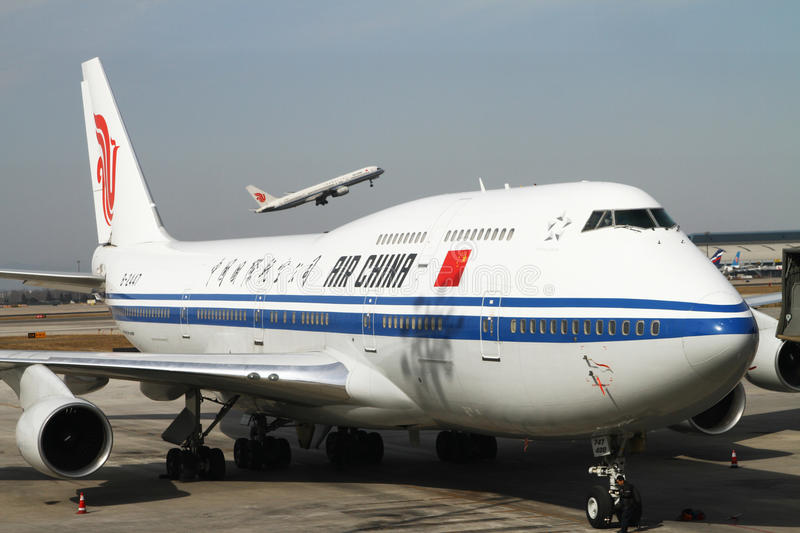 Air China Boing 747 Jumbo Jet. At the gate at Beijing Capital International Airport Terminal 3, with aircraft taking off in the background stock photos