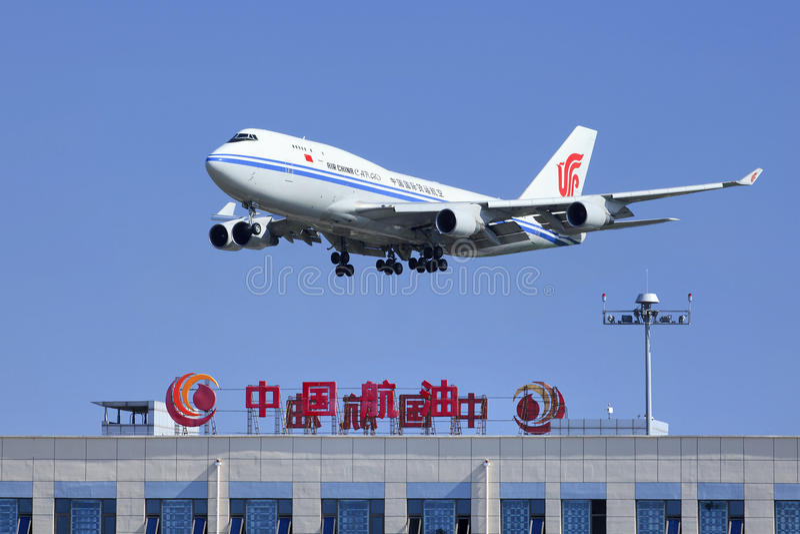 Air China Cargo Boeing 747-412BCF, B-2453 skims over China Aviation Oil Corp. building, Beijing, China. BEIJING-JULY 5. Air China Cargo Boeing 747-412BCF, B-2453 royalty free stock photo