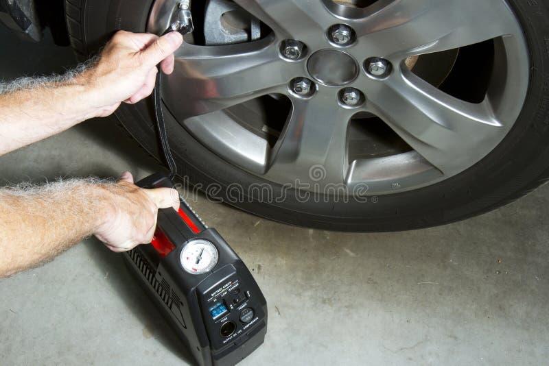 Air Compressor and Tire. Air compressor filling car tire stock images