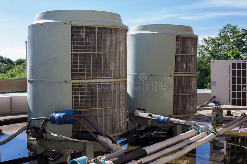 Air compressors on roof of factory stock image