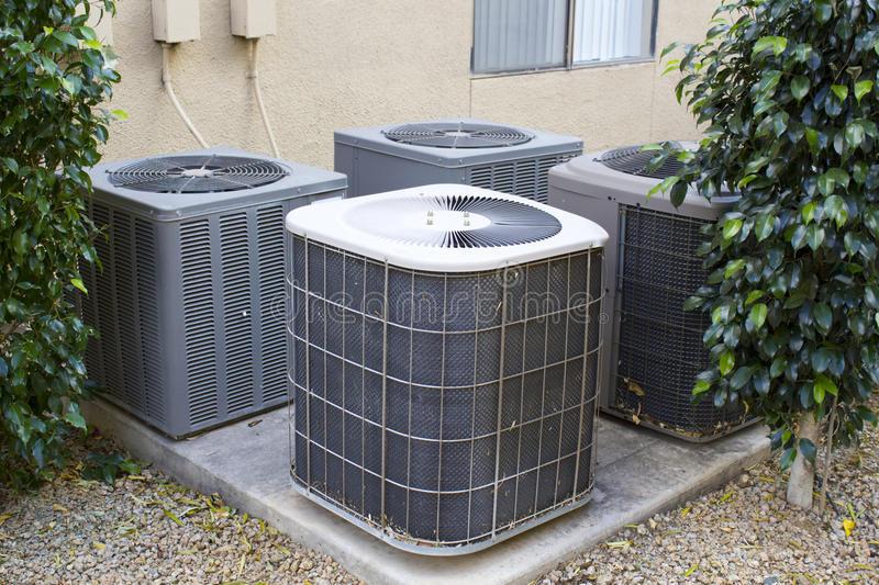 Air Conditioner Compressors. Residential air conditioner compressor units near building stock photo