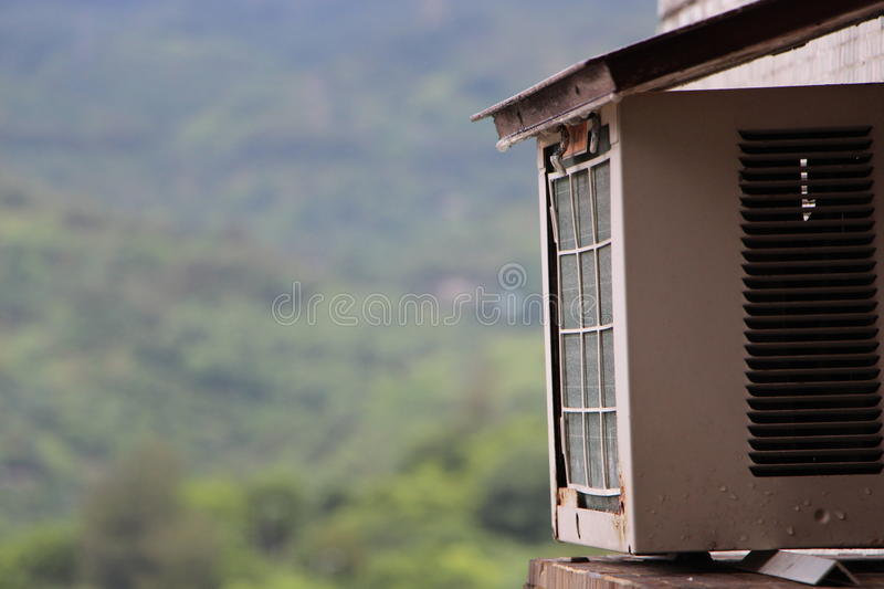 An air-conditioner feels Hot outside the house- Global Warming. An air-conditioner feels Hot outside the house- The Issue of Global Warming royalty free stock images