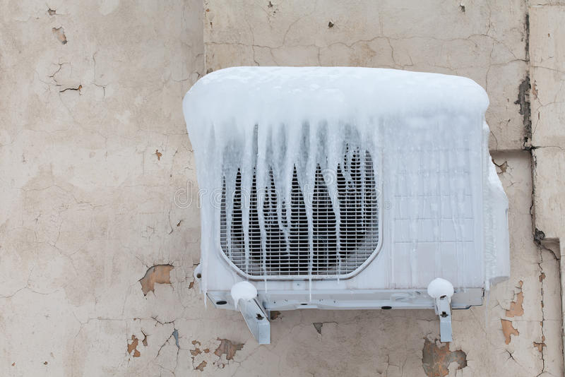 Air conditioner with frozen ice and icicles. Cooling, cold concept image. Aged wall background. Air conditioner with frozen ice and icicles. Cooling, cold royalty free stock images
