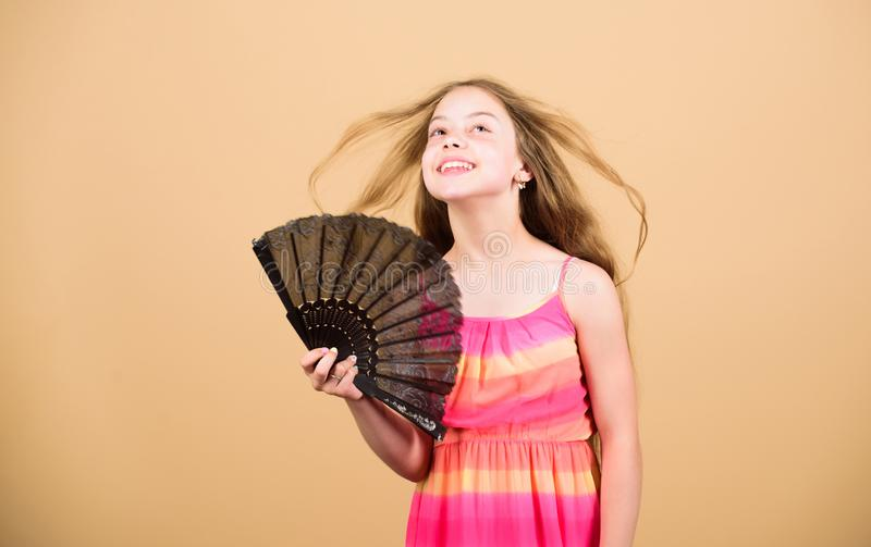 Air conditioner. Waving to create current air. Little girl waving elegant fan. Summer heat. Fresh air. Kid girl fanning royalty free stock photography