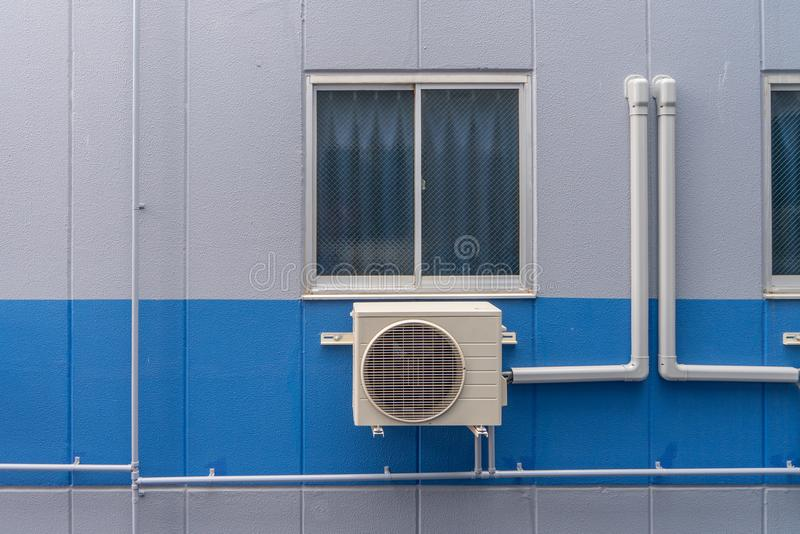 Air conditioning compressor system assembled on window of building.  royalty free stock photo