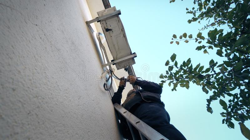 Air Conditioning Repair Young repairman on the ladder fixing air conditioning system stock images