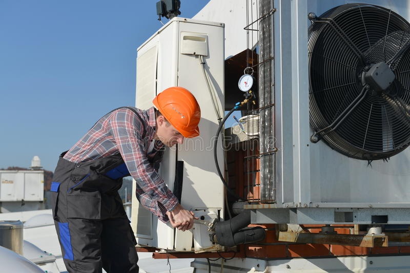 Air Conditioning Repair. Young repairman on the roof fixing air conditioning system. Model is actual repairman / electrician stock images