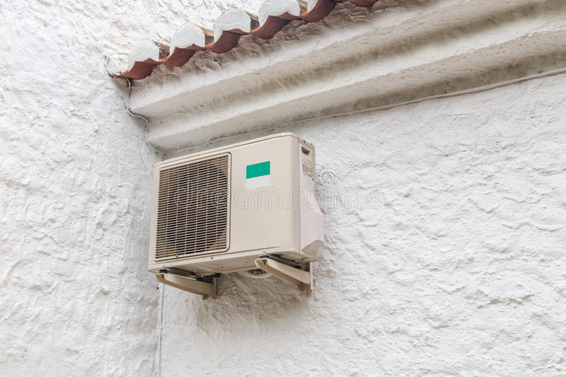 Air conditioning unit. Hanging outside a white house stock image