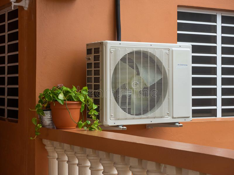 Air conditioning unit outside a residential house. High efficiency modern AC-heater unit, energy save solution-horizontal, outside a house royalty free stock image