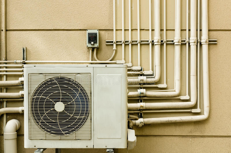 Air conditioning unit sitting outside. And Pipe Line on wall royalty free stock image