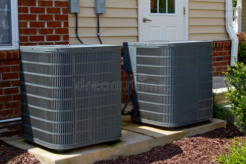Air Conditioning Units. Two air conditioning units set on concrete pads stock images