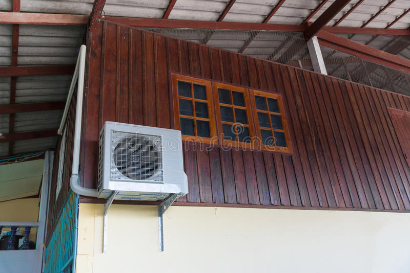 Air conditioning units installed outside the house. On wooden wall stock photo