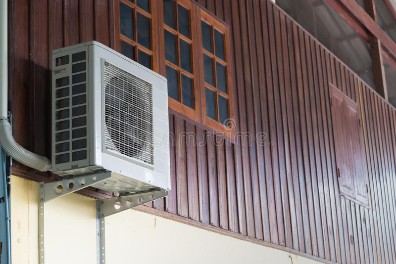 Air conditioning units installed outside the house. On wooden wall royalty free stock photos