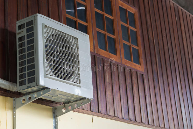Air conditioning units installed outside the house. On wooden wall stock photos