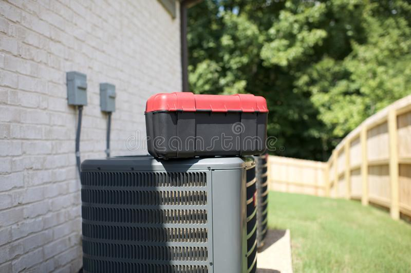 Air conditioning units in need of repair. A toolbox sitting on top of an heating and cooling unit in need of repairs stock photography