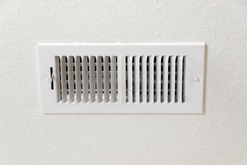 Air Conditioning Vent in Textured Wall Background With Copy Space. An AC/heating vent with plenty of copy space above and below royalty free stock photos