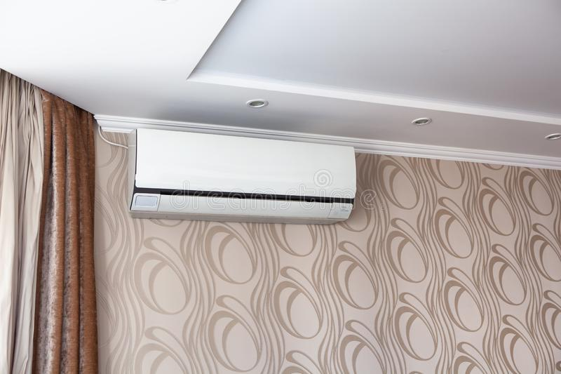 Air conditioning on the wall inside the room in apartment, switched off. Interior in calm beige tones.  stock photo