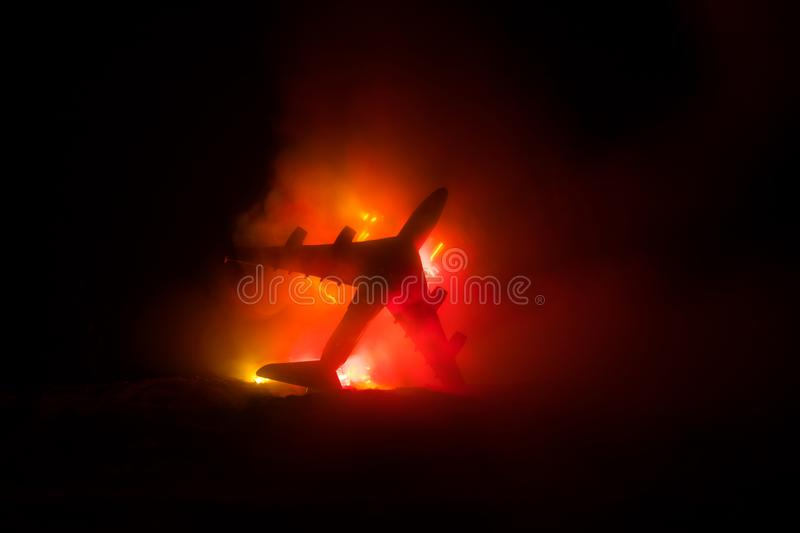 Air Crash. Burning falling plane. The plane crashed to the ground. Decorated with toy at dark fire background. Air accident stock image
