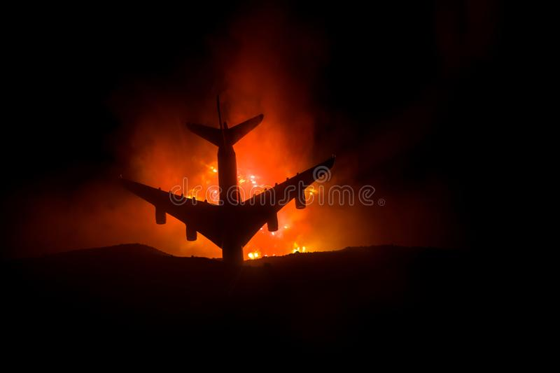 Air Crash. Burning falling plane. The plane crashed to the ground. Decorated with toy at dark fire background. Air accident royalty free stock image