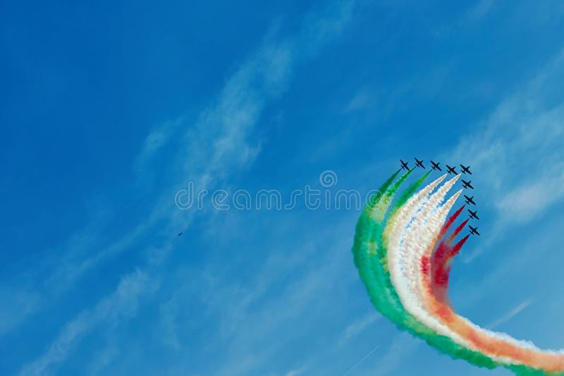 Air show. Air fighters on an air show flying in the shape of a geometric figure with colorful bright trails of smoke against a blue sky with clouds. Air stock photos