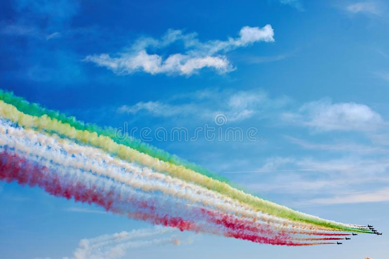 Air show. Air fighters on an air show flying in the shape of a geometric figure with colorful bright trails of smoke against a blue sky with clouds. Air royalty free stock images