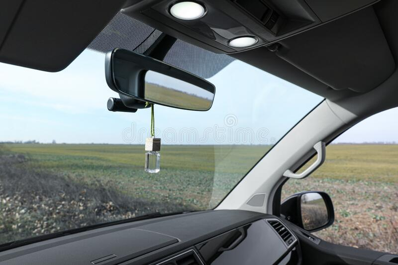 Air freshener hanging on rear view mirror. In car stock image