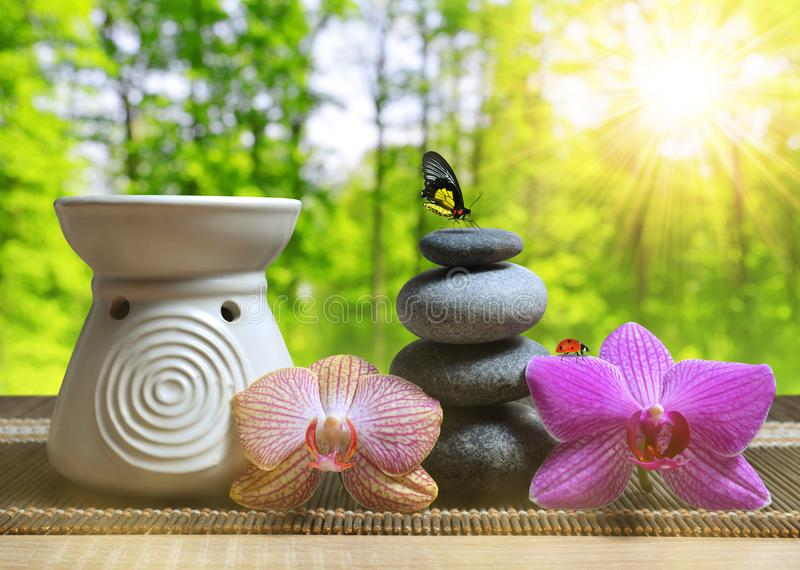 Air freshener with zen pebbles and orchid flowers on table. Spa and healthcare concept royalty free stock images