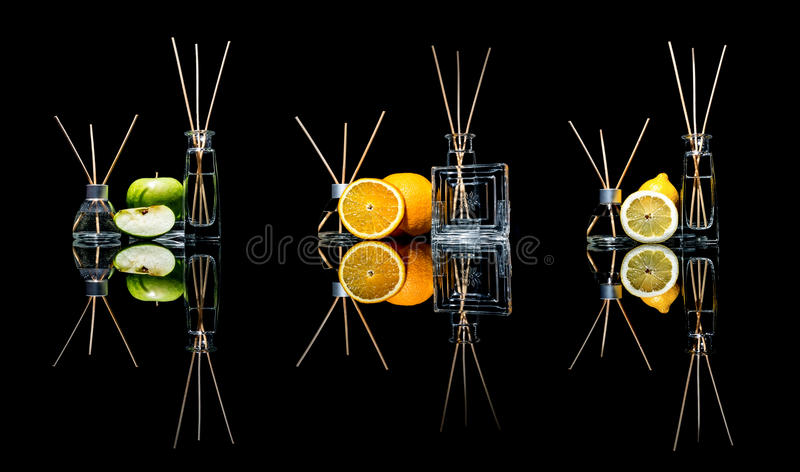 Air fresheners in a glass jars with sticks and lemon, green apple and orange with reflection isolated on a black royalty free stock image