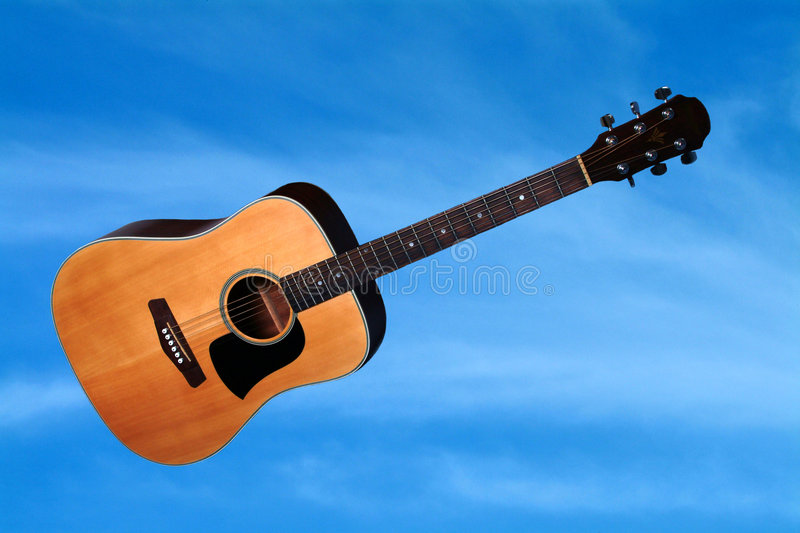 Air Guitar. Accoustic Guitar Against A Blue Sky Background royalty free stock photo