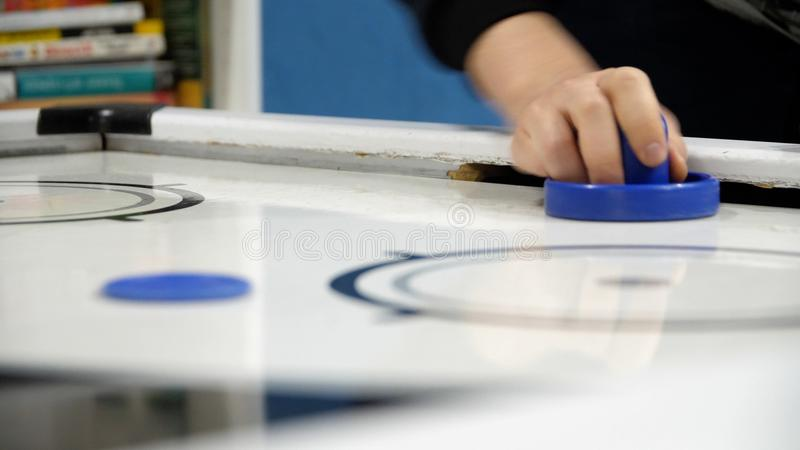 Air Hockey Game Playing in Arcade - Close Up. Close-up hands of man playing in an air hockey, scoring goals in the royalty free stock image