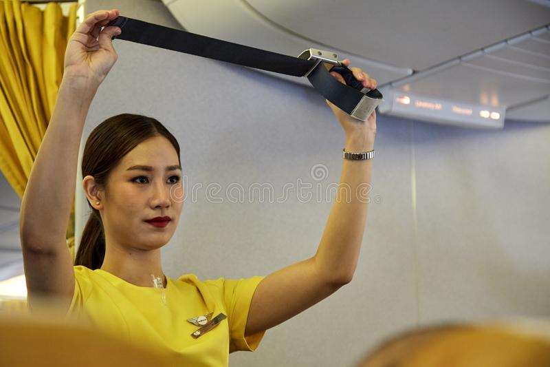 Air hostess demonstrate safety procedures. Bangkok Thailand, Jan 22 ,2019 , Airline nokscoot Interior of airplane with passengers on seats and stewardess in stock photo