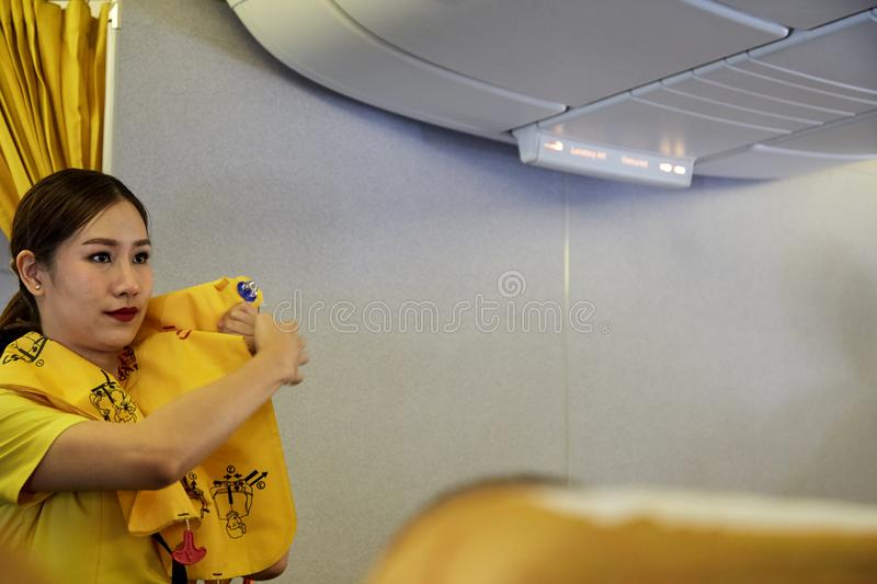 Air hostess demonstrate safety procedures. Bangkok Thailand, Jan 22 ,2019 , Airline nokscoot Interior of airplane with passengers on seats and stewardess in royalty free stock photos