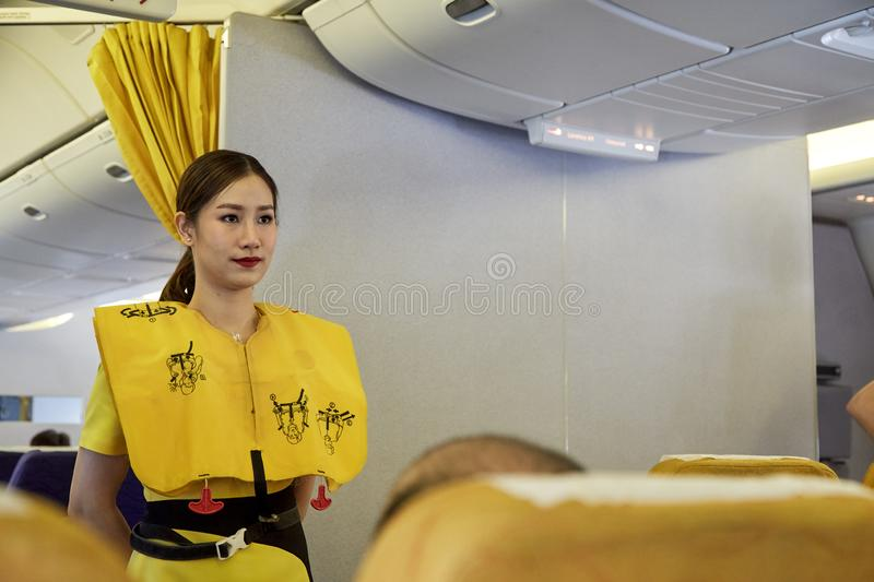 Air hostess demonstrate safety procedures. Bangkok Thailand, Jan 22 ,2019 , Airline nokscoot Interior of airplane with passengers on seats and stewardess in royalty free stock image