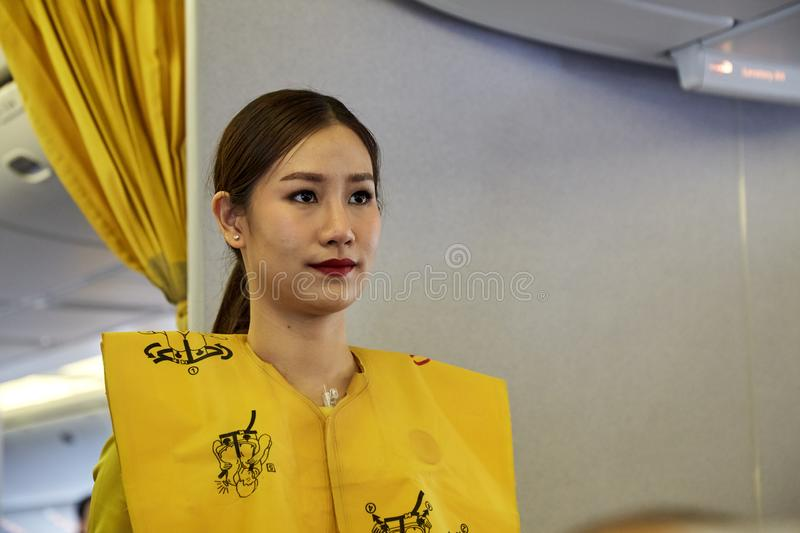 Air hostess demonstrate safety procedures. Bangkok Thailand, Jan 22 ,2019 , Airline nokscoot Interior of airplane with passengers on seats and stewardess in royalty free stock photo